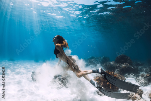 Fototapeta Woman freediver with fins swim over sandy bottom and sun rays underwater ocean
