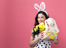 Young Woman With Easter Basket On A Pink Background