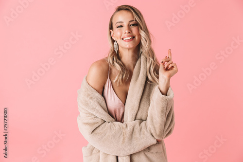 Fototapeta Pretty woman posing isolated over pink wall background dressed in fashion coat. obraz