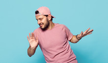 Young Cheerful Bearded Man In Stylish Clothes And Pink Baseball Cap Dancing Happily On Blue Background
