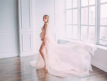 Cute Young Slim Lady With Tummy In Spacious Room With White Walls And Large Windows, Pregnant Girl With Blond Hair Twisted In A Long Pink Gentle Lace Peignoir With Flying Train Posing For Camera