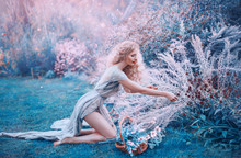 Field Mermaid Collects Herbs And Flowers In Small Basket. Slender Forest Nymph Sits On Her Knees In Long Light Dress With Open Bare Legs And Back, Glare Of Bright Sun In Magical Purple And Blue Glade