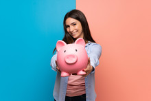 Young Woman Over Pink And Blue Wall Holding A Piggybank