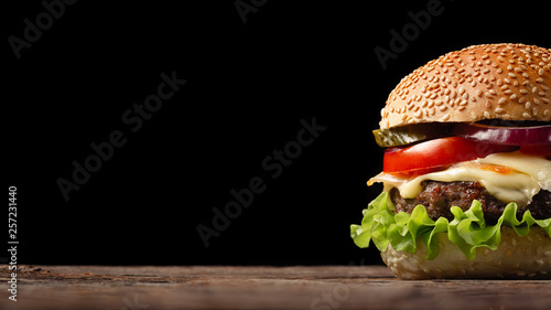 Homemade hamburger close-up with beef, tomato, lettuce, cheese and onion on wooden table Fototapet