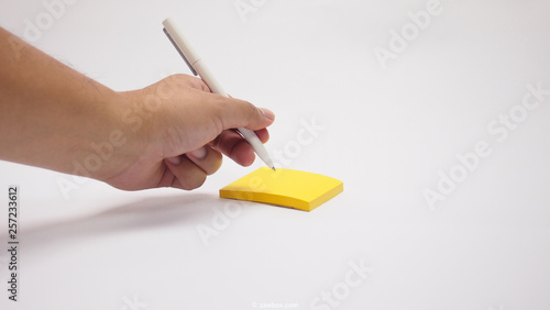 Photo white background for left hand writing with pen on yellow small paper