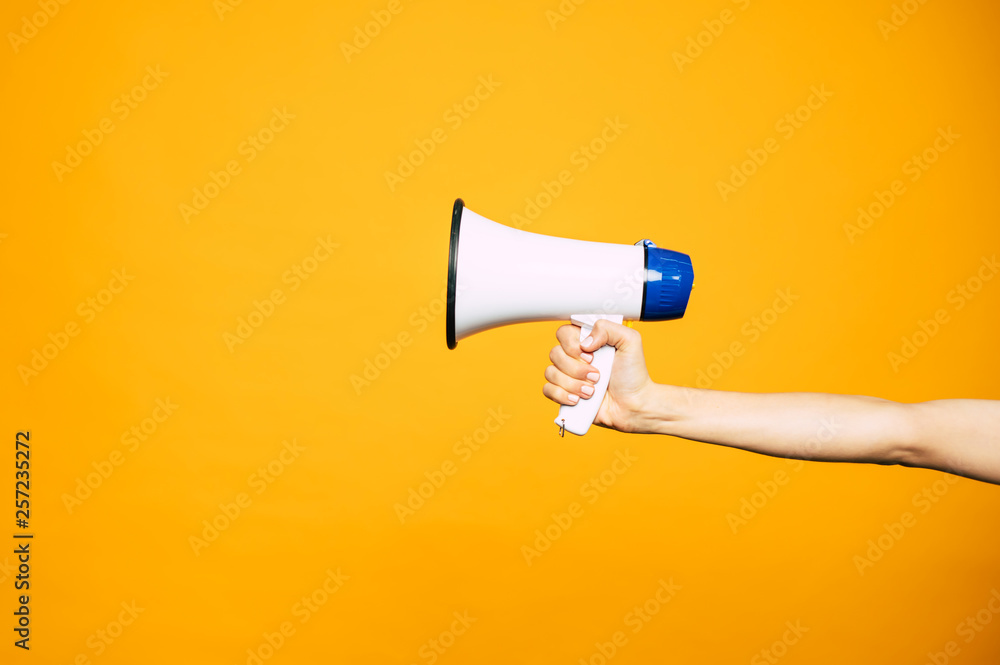 Fototapeta In a bull voice. A yellow background with a woman's hand in front of it holding three colored  megaphone of white, black and blue colors.