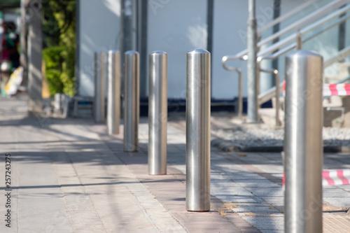 Fotomural stainless steel bollards on footpath.