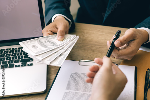 Fotografie, Obraz  Partner has made a fraud in the contract of sale and being handed a cash and pen to the businessman signing the contract corruption bribery concept