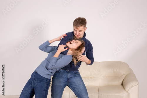 Fotografie, Obraz  people, abuse and violence concept - agressive man strangling his wife
