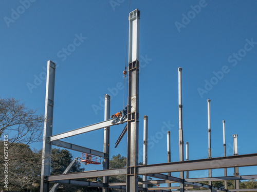 Valokuva 2 ironworkers is straddle a horizontal steel I-beam and reach out to grab another beam to move into place