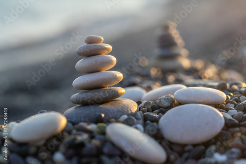 Photo sur Plexiglas Zen pierres a sable Stones pyramid on pebble beach symbolizing stability, zen, harmony, balance. Shallow depth of field.