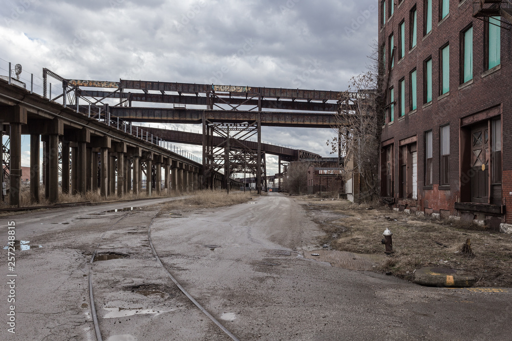 Fototapeta Crossing elevated train tracks and vintage red brick abandoned factory