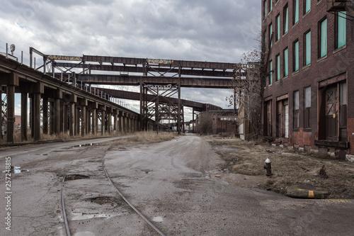Billede på lærred Crossing elevated train tracks and vintage red brick abandoned factory