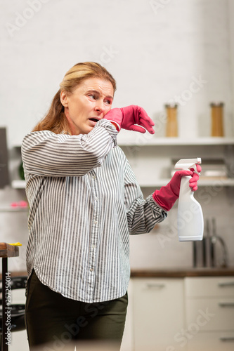 Fotografie, Obraz  Housewife wearing trousers and shirt having allergy to dust