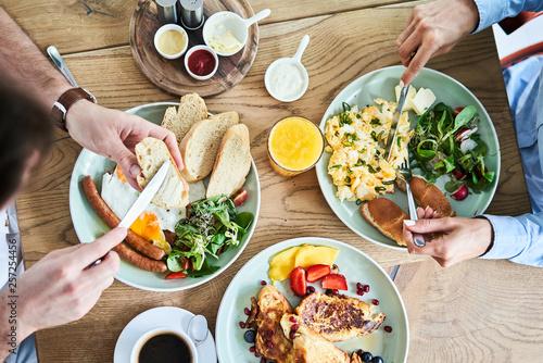 Fototapeta Overhead picture of couple eating tasty breakfast at restaurant. obraz
