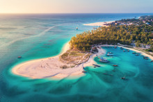Aerial View Of The Fishing Boats On Tropical Sea Coast With Sandy Beach At Sunset. Summer Holiday On Indian Ocean, Zanzibar, Africa. Landscape With Boat, Green Trees, Transparent Blue Water. Top View