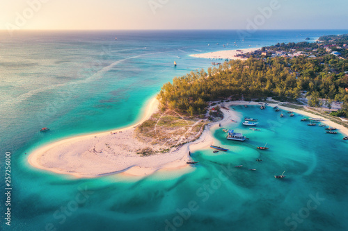 Spoed Fotobehang Zanzibar Aerial view of the fishing boats on tropical sea coast with sandy beach at sunset. Summer holiday on Indian Ocean, Zanzibar, Africa. Landscape with boat, green trees, transparent blue water. Top view