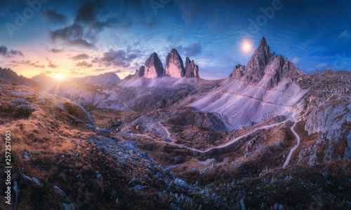 Foto auf Leinwand Landschaft Mountain valley at beautiful sunset. Autumn landscape with mountains, hills, stones, grass, blue sky with clouds and moon at night. High rocks at dusk. Twilight in Tre Cime in Dolomites, Italy. Travel