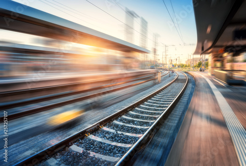 Tuinposter Spoorlijn Railway station with motion blur effect at sunset. Industrial landscape with railroad, blurred railway platform, sky with orange sunlight in the evening. Railway junction in Europe. Transportation