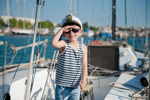 Fotografía  cute happy caucasian kid in captain cap and sunglasses on yacht board in summer