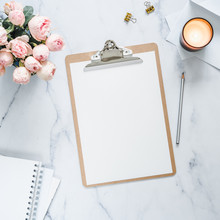 Top View Of Clipboard With White Empty Page. Clipboard, Flowers, Scented Candle On White Marble. Feminine Home Office Mock Up With Blank Sheet Of Paper A4 Portrait Format,copy Space For Text. Flat Lay