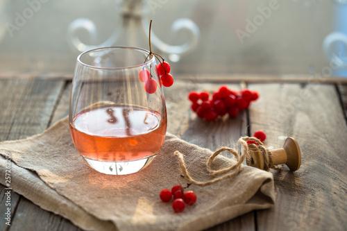 Recess Fitting Tea hot viburnum tea in a glass with on a gray wooden table, next to fresh viburnum berries. viburnum healthy tea