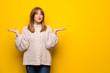 Leinwandbild Motiv Redhead woman over yellow wall having doubts while raising hands