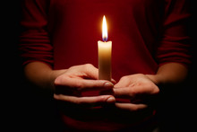 Bright Candle Light In The Hands Of The Girl.  Faith In God.  Prayer With Candles In Hand.  Woman Praying With Candles In Her Hands, Close-up.