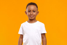 Isolated Image Of Cute Adorable Dark Skinned Schoolboy Wearing White T-shirt Posing In Blank Yellow Studio With Confident Cheerful Smile Because He Received High Marks For Maths Test At School
