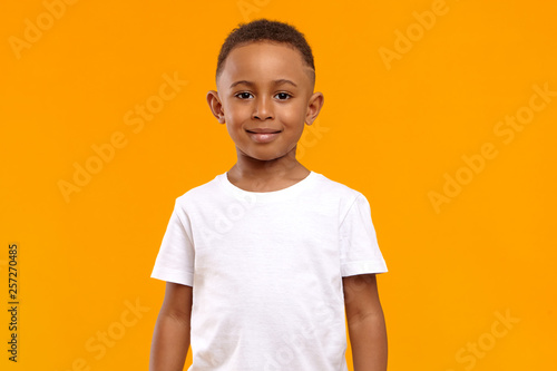 Fototapeta Isolated image of cute adorable dark skinned schoolboy wearing white t-shirt pos