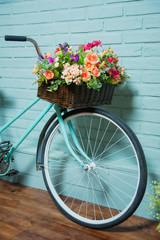 Fototapeta na wymiar Bicycle with a basket of flowers. Blue brick wall. Summer decor. Decorative brickwork. Wicker basket with flowers.