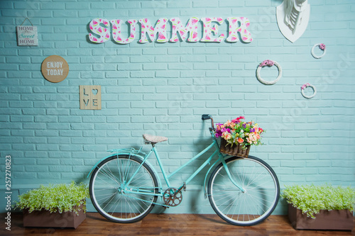 Foto op Plexiglas Fiets Bicycle with a basket of flowers. Blue brick wall. Summer decor. Photo frames on the wall. Linoleum in the form of parquet. Baskets of green plants. Decorative brickwork.