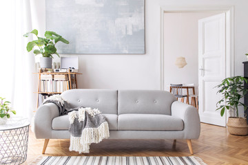 Stylish scandianvian living room with design sofa with elegant blanket, coffee table and bookstand on the white wall. Brown wooden parquet. Concept of minimalistic decor interior with piano. Mock up.