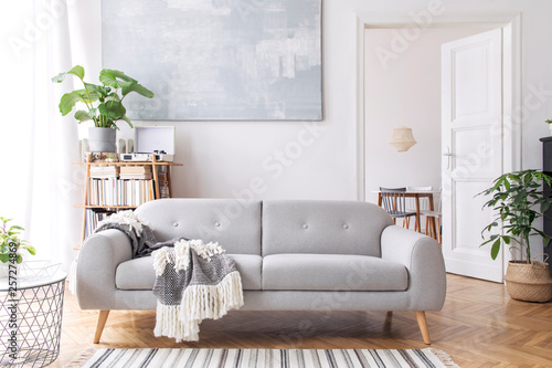 Fotografie, Obraz  Stylish scandianvian living room with design sofa with elegant blanket, coffee table and bookstand on the white wall