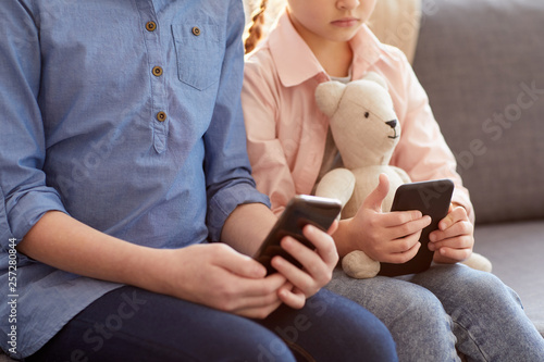 Photo Closeup of two children using smartphones at home texting and scrolling through