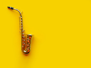 Saxophone on bright yellow background. Wind musical instruments. Copy space f...