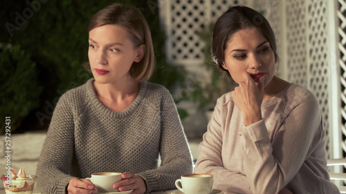 Fotografie, Tablou Two upset female friends sitting in cafe, relations conflict, misunderstanding