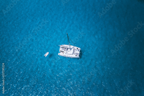 Fototapeta Aerial drone photo of catamaran boat at blue clear ocean water