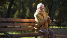 Happy Aged Woman Enjoying Warm Sunny Day Sitting On Bench In Park, Retirement