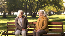 Two Old Fiends Talking And Laughing Sitting On Bench In Park, Retirement Age