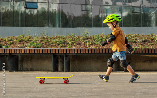 Cuadros en Lienzo A little boy enjoys a yellow cruiser penny plastboard