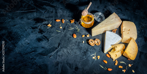 Fototapeta Different kinds of cheese with nuts and honey on dark background, copy space obraz