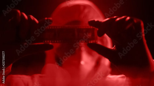Fotomural  Man in lab costume watching camera roll, developing photograph in red light