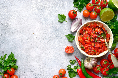Foto Tomato salsa (salsa roja) - traditional mexican sauce  with ingredients for making on a light grey slate,stone or concrete background