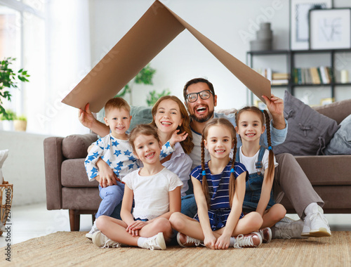 Fototapeta concept of housing and relocation. happy  big family mother father and kids with roof at home . obraz