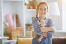 Waist Up Portrait Of Happy Red Haired Girl Hugging Plush Toy And Looking At Camera Lit By Warm Sunlight, Copy Space