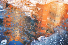 Reflection Of A House In An Ice Puddle In Spring. Melting Snow.