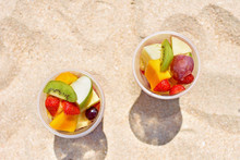 Delicious Fruit Salad In Plastic Cup On Beach