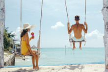 Teenage Girl And Boy Hanging On Swings With A Sea View In Beach Cafe