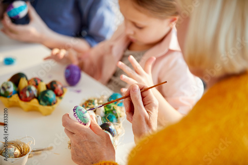 High angle portrait of unrecognizable mature woman painting Easter eggs in art c Fototapeta
